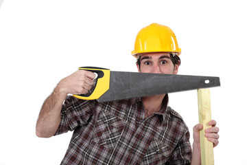 Tradesman hiding behind a saw