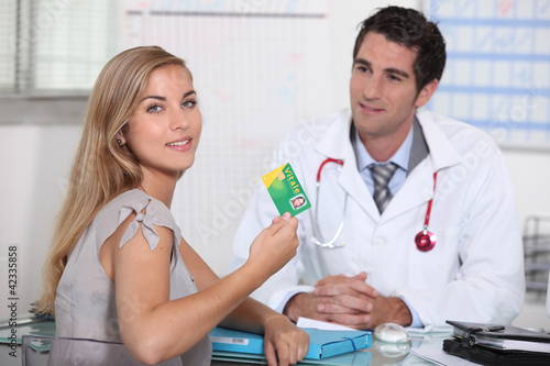 Teenager showing French health insurance card