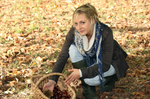 woman in woods picking up chestnuts