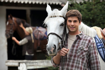 A young man with a horse.