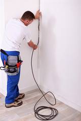 Electrician fixing a wire to a wall