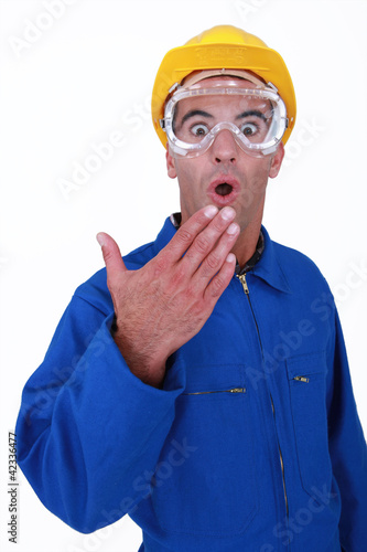 Shocked manual worker wearing safety glasses