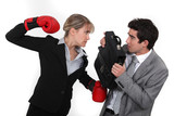 Businessman with boxing gloves hitting man