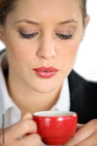 Woman blowing a hot drink