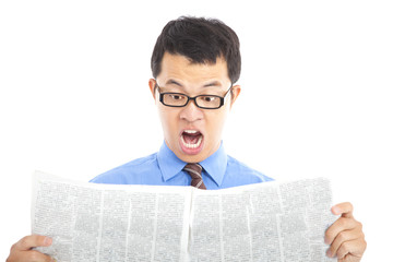 surprised businessman watching the newspaper