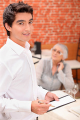 Young waiter taking an order in a restaurant