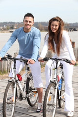 Young couple riding bikes along a river