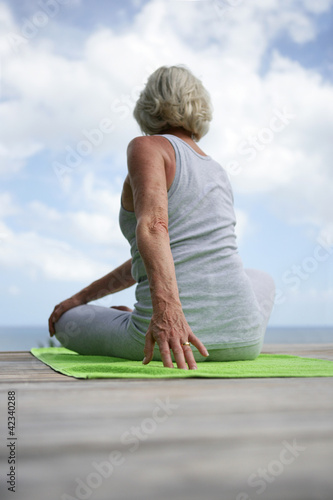 Woman performing yoga moves on wooden jetty