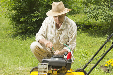 Mid age man repairing lawn mower in the garden
