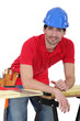 Construction worker leaning against his workbench