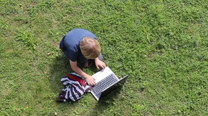 Kind läuft zum Laptop und setzt sich