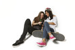 Two young  skateboarding girl friends looking at phone