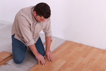 Man laying a wooden floor