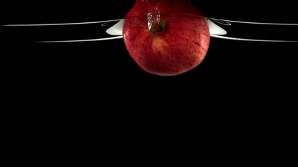 Apple in water on black background, Slow Motion