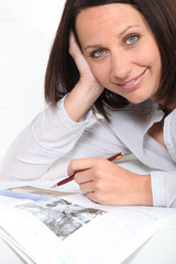 Brunette using pen to highlight magazine articles