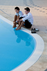 Young couple relaxing by pool