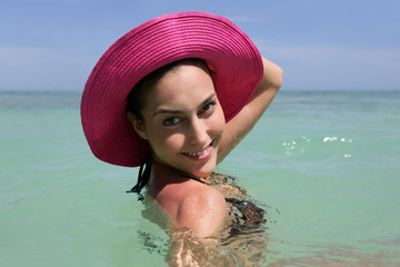 Woman in a pink hat on the beach