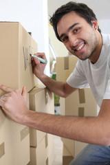 Man marking cardboard boxes