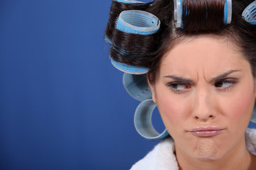 Unhappy woman with hairroller on.