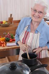 Elderly woman cooking in her kitchen