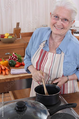 Elderly woman cooking in her kitchen