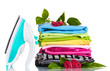 Pile of colorful clothes and electric iron with roses isolated