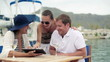Young ritch friends with tablet computer sitting in marina