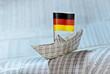 Papierschiff mit deutscher Flagge auf Börsennachrichten