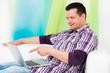 lachender mann zeigt mit dem finger auf sein notebook