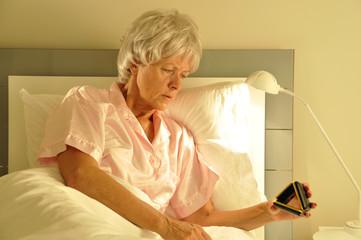 seniorin im Bett mit Wecker