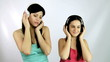 Two beautiful girls listening music with headphones