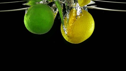 Lemon and lime in water on black background, Slow Motion