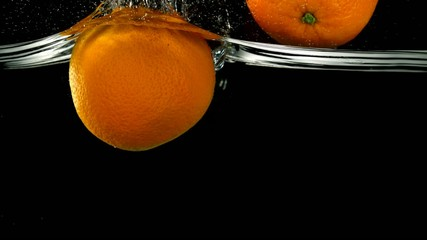 Orange in water on black background, Slow Motion