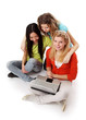 Three girls working with a laptop, sitting on the floor,