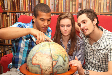 friends planning a journey and looking at a globe
