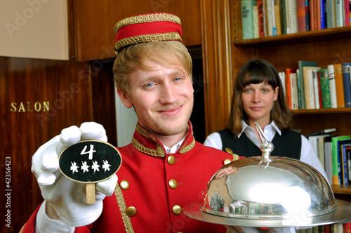 Hotelpage mit Tafel und Schriftzug 4 Sterne mit Zimmermädchen