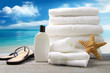 White towels and sandals with ocean scene