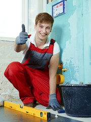 Apprentice for sanitary installations at work shows thumb up