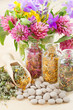 different healing herbs in glass bottles, flowers bouqet, tablet