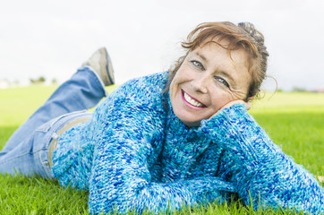 happy smiling mature woman laying on grass
