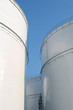 Tall white storage tanks at an oil refinery