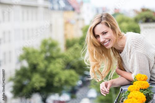 Frau genießt Aussicht vom Balkon