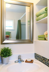New beautiful white sink with green towels and mirror.