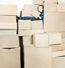 Boy holding box is sitting on the top of heap of carton packed b