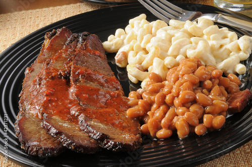 Closeup up of beef brisket with baked beans