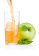 Pouring apple juice into a glass, green apples with green leaf o