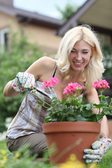 Portrait of a beautiful blonde with a pot of flowers