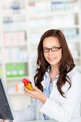 lächelnde apothekerin mit medikament