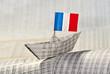 Papierschiff mit französischer Flagge auf Börsennachrichten