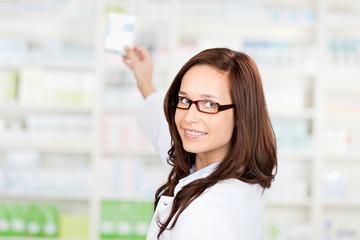 apothekerin nimmt medikament aus dem regal